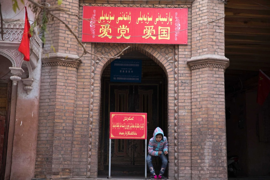 """A child rests near the entrance to a mosque where a banner in red reads """"Love the party, Love the country""""."""