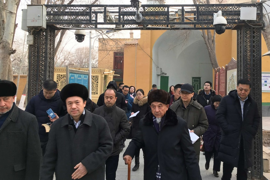Imams and government officials pass under security cameras at a mosque in Kashgar, China.