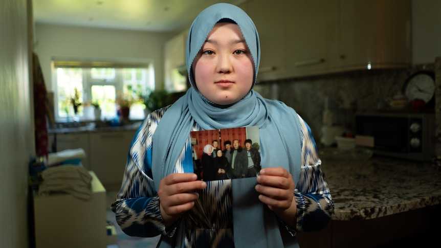 A woman in a headscarf poses with a photo of family members in her hands.