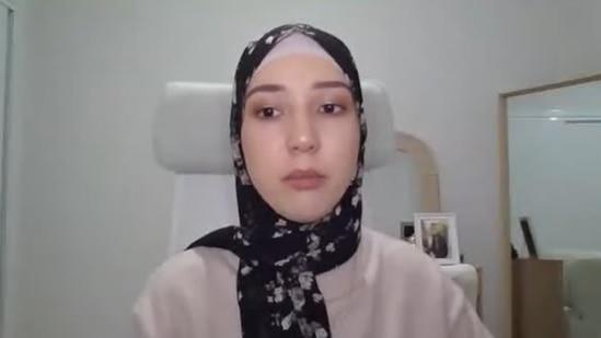 A woman wearing a headscarf speaks via video call
