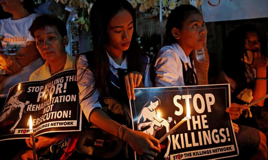 Protesters hold lighted candles at the wake of Kian Loyd delos Santos